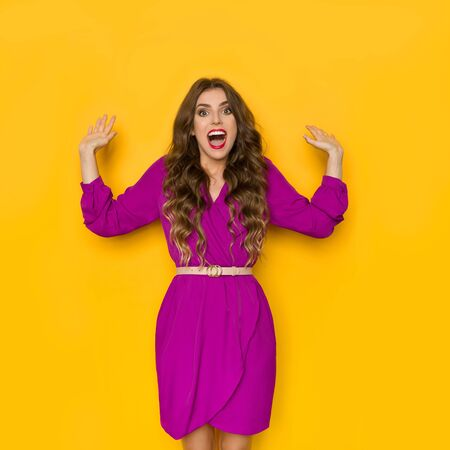 Excited beautiful young woman in purple dress is holding hands raised, looking at camera and shouting. Three quarter length studio shot on yellow background.