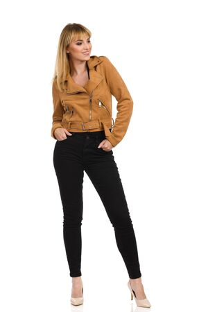 Beautiful confident young woman in brown suede leather jacket, black jeans and high heels is standing, holding hands in pockets and looking away. Front view. Full length studio shot isolated on white.