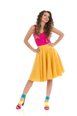 Smiling young woman in colorful high heels, vibrant yellow skirt and pink top is standing legs apart and holding hands on hip. Front view. Full length studio shot isolated on white.