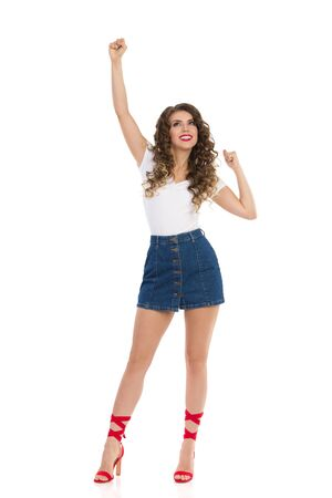 Beautiful young woman in jeans mini skirt, white top and red high heels is standing with fist raised and looking up. Front view. Full length studio shot isolated on white.