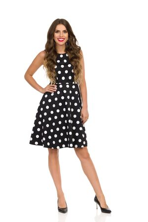 Beautiful young woman in black cocktail dress in polka dots and high heels is standing, holding hand on hip and smiling. Front view. Full length studio shot isolated on white.