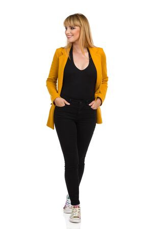 Beautiful young woman in yellow jacket, black jeans and vibrant sneakers is walking towards camera, looking away and smiling. Front view. Full length studio shot isolated on white.