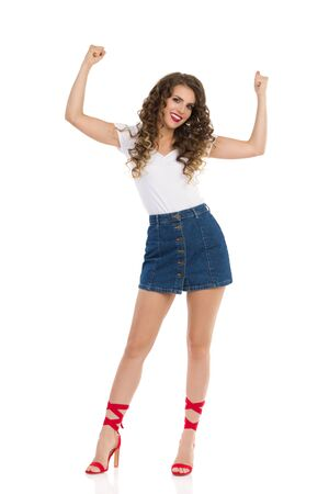 Beautiful young woman in jeans mini skirt, white top and red high heels is standing with arms raised and flexing muscles. Front view. Full length studio shot isolated on white. Stock Photo