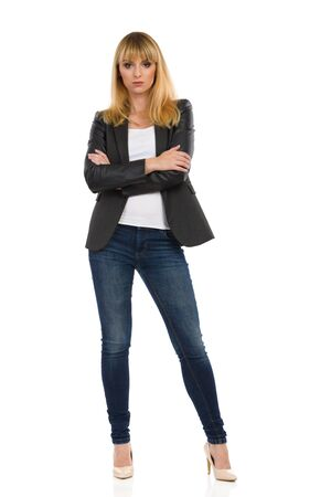 Serious young businesswoman in unbuttoned black suit, jeans and high heels is standing and holding arms crossed. Full length studio shot isolated on white.