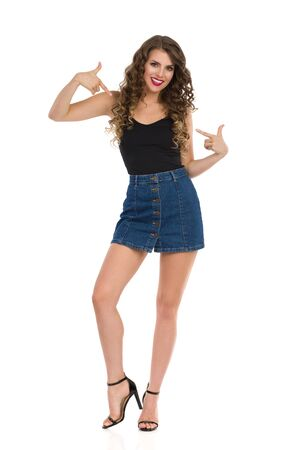 Young confident woman in jeans mini skirt, black top and high heels is standing, pointing at herself and smiling. Full length studio shot isolated on white.