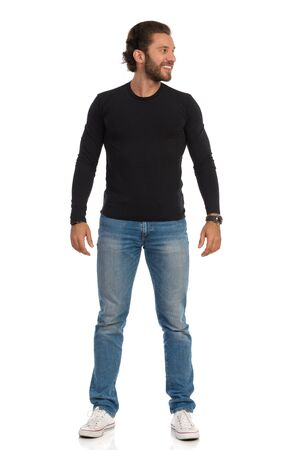 Smiling handsome man in black jersey, jeans and sneakers is standing relaxed and looking at the side. Front view. Full length studio shot isolated on white. Zdjęcie Seryjne