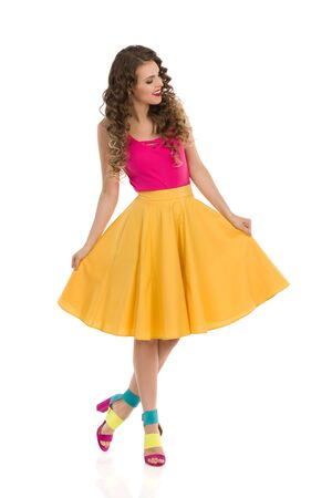 Cheerful young woman is standing and presenting her circle cut yellow skirt. Full length studio shot isolated on white. Stock Photo