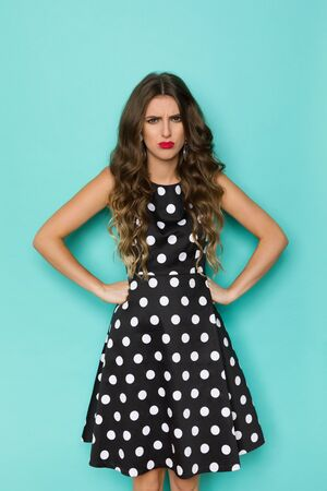 Angry young woman in black cocktail dress in polka dots pattern is holding hands on hip and looking at camera. Three quarter length studio shot on turquoise background. Standard-Bild