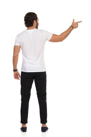 Handsome young man in moccasins, black jeans, and white sneakers is standing, looking away and pointing at the side. Rear view. Full length studio shot isolated on white. Stock fotó