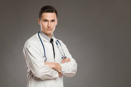 Portrait of a serious male doctor with arms crossed. Waist up studio shot on gray background. Banque d'images - 144163787