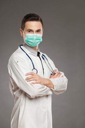 Young male doctor wearing surgical mask and holding arms crossed. Waist up studio shot on gray background. Banque d'images - 144163954