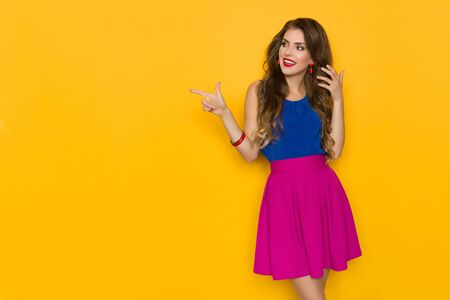 Beautiful young woman in vibrant clothes is pointing at the side and talking. Three quarter length studio shot on yellow background.