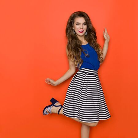 Carefree young woman in striped mini skirt and blue top is standing on one leg, looking at camera and smiling. Three quarter length studio shot on orange background. 版權商用圖片