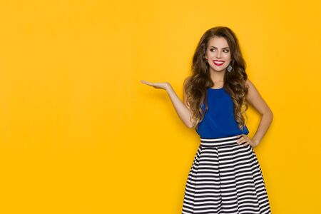 Cute smiling woman in striped skirt and blue top is holding hand raised, presenting and looking away. Three quarter length studio shot on yellow background.