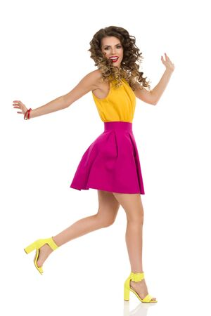 Happy young woman in yellow top, pink mini skirt and colorful high heels is standing on one leg and jumping or running. Front view. Full length studio shot isolated on white. Stockfoto