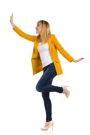 Excited young woman in unbuttoned yellow jacket is standing on one leg, waving for somebody, looking away and shouting. Side view. Full length studio shot isolated on white.