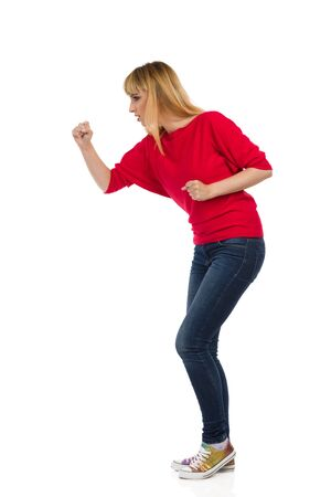 Angry young woman in red blouse and sneakers stands with raised fist and threatens. Side view. Full length studio shot isolated on white.