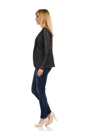 Beautiful young businesswoman in black suit, jeans and high heels is standing, looking away and smiling. Side view. Full length studio shot isolated on white.