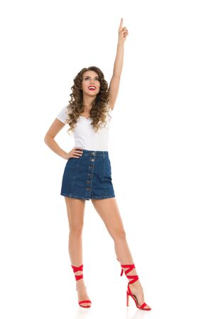 Young woman in jeans mini skirt, white top and red high heels is pointing over head and looking up. Full length studio shot isolated on white.
