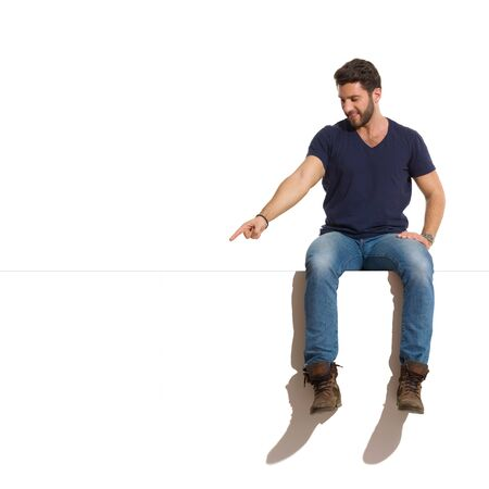 Happy young man in boots, jeans and blue shirt is sitting on a top, looking down and pointing. Full length studio shot isolated on white.
