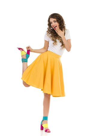 Excited beautiful young woman in yellow skirt, white top and colorful high heels stands on one leg, holds the shoe by the heel and shouting. Full length studio shot isolated on white.