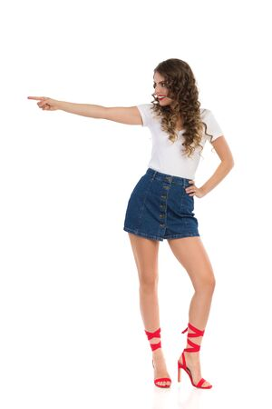 Confident young woman in white top, jeans mini skirt and red high heels is pointing at the side and looking away. Front view. Full length studio shot isolated on white.