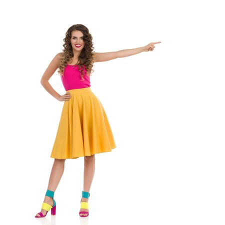Beautiful young woman in colorful high heels, vibrant yellow skirt and pink top standing and pointing at the side. Front view. Full length studio shot isolated on white. Foto de archivo