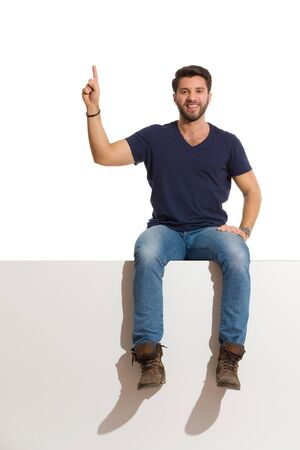Smiling young man in boots, jeans and blue shirt is sitting on a top, with arm raised, pointing up and looking at camera. Full length studio shot isolated on white. Foto de archivo