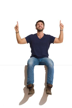 Handsome smiling man in boots, jeans and blue shirt is sitting on a top, with arms raised, looking up and pointing above head. Full length studio shot isolated on white.