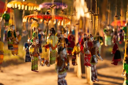 Colorful Burmese handmade wooden puppet in traditional clothes on hanging on strings on a tree at the market in Bagan