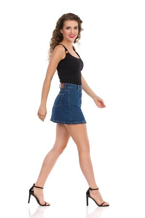Beautiful young woman in jeans mini skirt, black top and high heels is walking, looking at camera and smiling. Side view. Full length studio shot isolated on white.