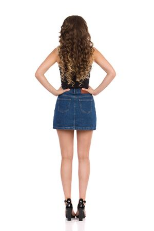 Rear view of standing young woman in jeans mini skirt, black top and high heels. Full length studio shot isolated on white.