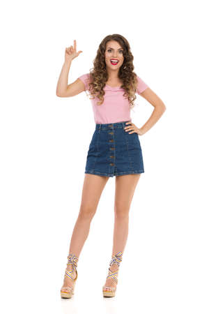 Happy young woman in jeans mini skirt, pink top and wedge shoes is standing, holding hands behind head, looking away and talking. Front view. Full length studio shot isolated on white.