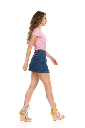 Beautiful smiling young woman in jeans mini skirt, pink top and wedge shoes is walking. Side view. Full length studio shot isolated on white.