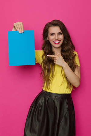 Smiling beautiful young woman is pointing at empty blue sheet of paper. Front view. Three quarter length studio shot on pink background.