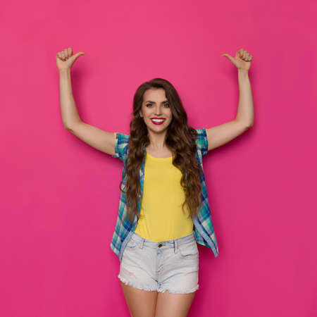 Young woman in unbuttoned lumberjack shirt is standing, holding arms raised and showing thumbs up. Three quarter length studio shot on pink background.