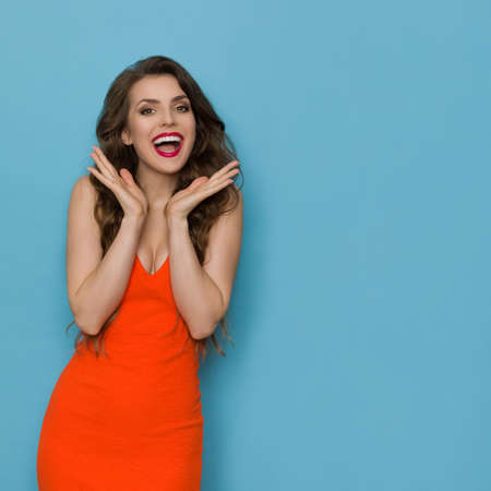 Excited young woman in orange dress is holding hands raised and shouting. Front view. Three quarter length studio shot on blue background.