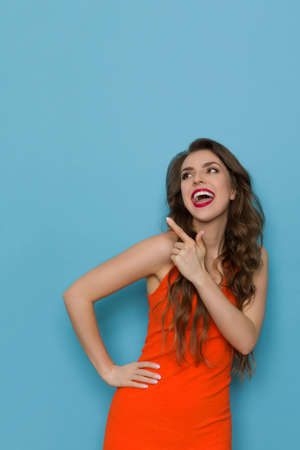 Happy young woman in orange dress is pointing up, looking away and talking. Front view. Three quarter length studio shot on blue background.