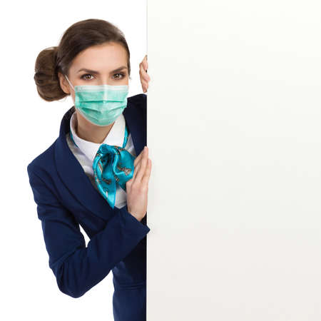 Young woman wearing protective face mask, blue suit and turquoise scarf is standing behind white banner and looking at camera. Waist up studio shot isolated on white.
