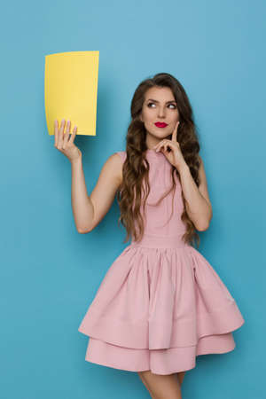 Beautiful young woman in pink cocktail dress is holding empty yellow sheet of paper, looking at it and thinking. Front view. Three quarter length studio shot on blue background. Standard-Bild