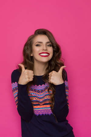Cute smiling woman in sweater with colorful pattern shows thumbs up. Waist up studio shot on pink background.