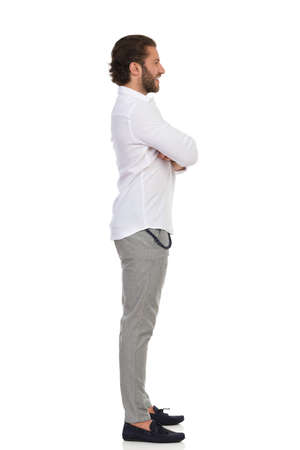 Young man in moccasins, gray trusers, and white shirt is standing with arms crossed and looking away. Side view. Full length studio shot isolated on white.