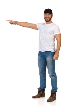 Handsome man wearing boots, jeans, white t-shirt and black cap is standing, looking at camera and directing. Full length studio shot isolated on white.