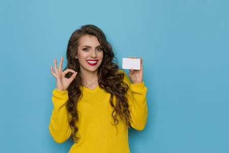 Smiling young woman in yellow sweater holds white card and shows ok hand sign. Waist up studio shot on blue background.