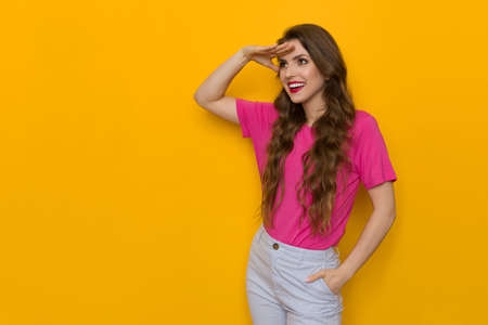 Happy young woman in pink shirt is hols hand on forehead, salutes and looks away. Three quarter length studio shot on yellow background. Reklamní fotografie