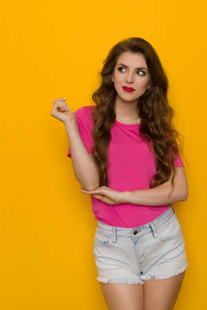 Pensive young woman in pink t-shirt and jeans shorts is standing and looking at the side. Front view. Three quarter length studio shot on yellow background.