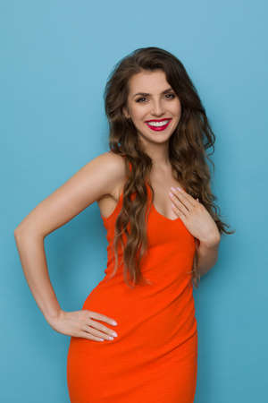 Beautiful young woman in orange dress is posing with hand on chest and smiling. Front view. Three quarter length studio shot on blue background. Banque d'images