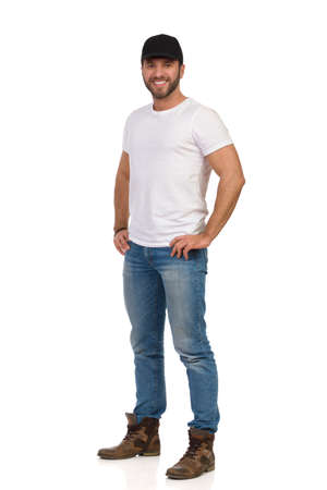 Casual man wearing boots, jeans, white t-shirt and black cap is standing relaxed with hand on hip. Full length studio shot isolated on white.