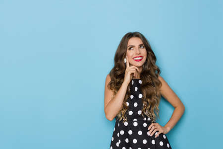 Young beautiful woman in black cocktail dress in polka dots pattern holds hand on chin, looks up, smiles and thinks. Waist up studio shot on blue background.