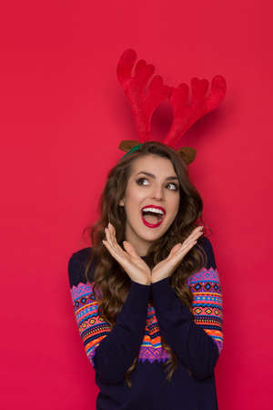 Happy young woman in sweater with colorful pattern wearing christmas reindeer horns, looking away and shouting. Waist up studio shot on red background.